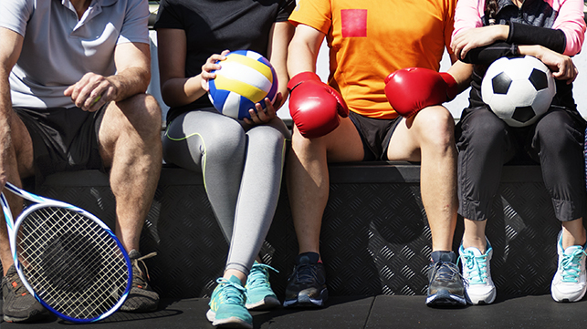 People on bench holding sport equipment