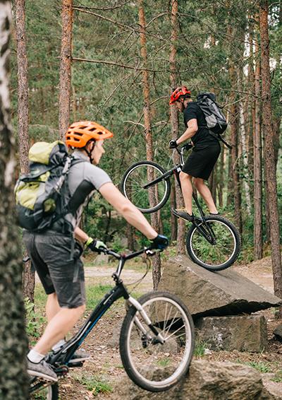 two men mountain biking in forest