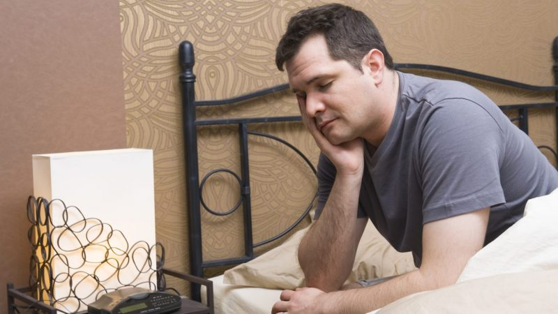 man sitting on bed suffering with fatigue